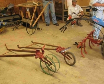 High-wheel cultivator (rear), double-wheel (L) and single-wheel (center) wheel hoes, and cultivator attached to BCS walk-behind tractor.