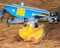 """Rotary plow attachment for BCS walk-behind tractor – as Luke Freeman says, the rotary plow is """"like a post-hole digger that is dragged through the soil. As the rotary plow turns, it drives itself downward while kicking up soil to one side."""""""