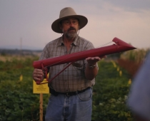 George Kuepper demonstrates transplanting with the Stand 'N Plant transplanter.